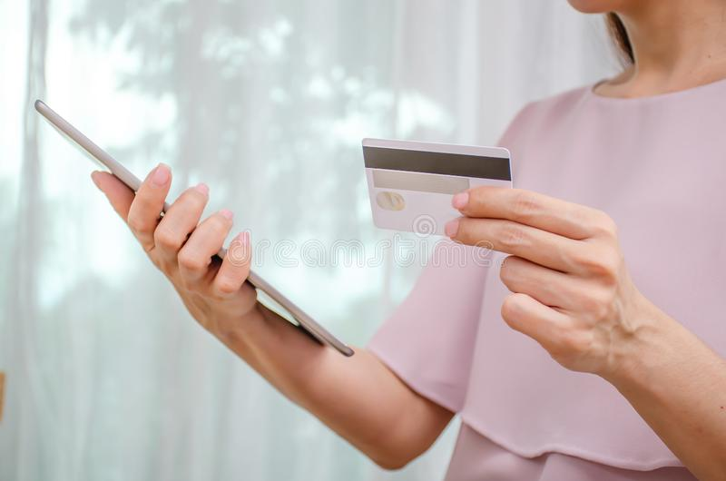 Female hands holding discount credit card in hand paying for shopping online at tablet, Youth casual lifestyle royalty free stock photography