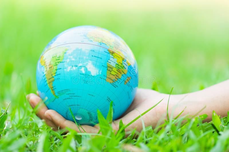 Female hands holding floating earth on natural green background. royalty free stock photo