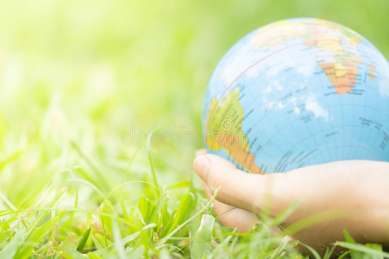 Female hands holding floating earth on natural green background. stock photo