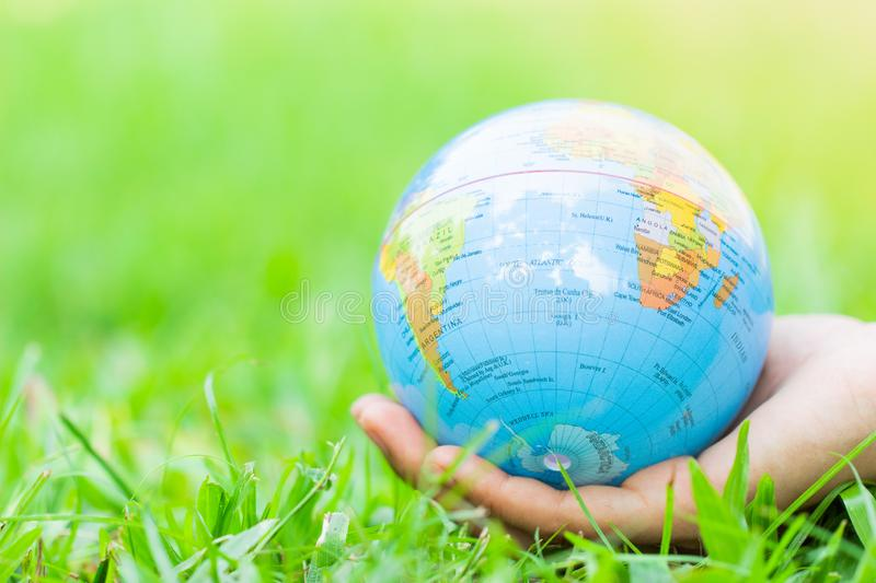 Female hands holding floating earth on natural green background. stock photography