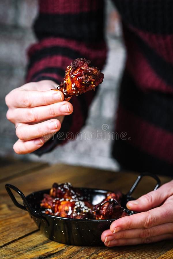 Female hands holding fried chicken wing royalty free stock photo