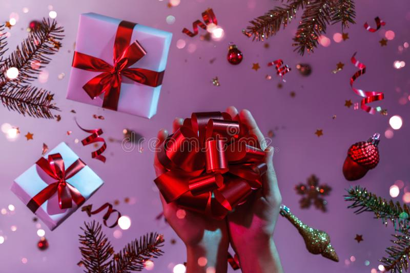 Female hands holding gift bow on colorful bright neon blue and purple background with flying Christmas decorations, fir branches stock photo