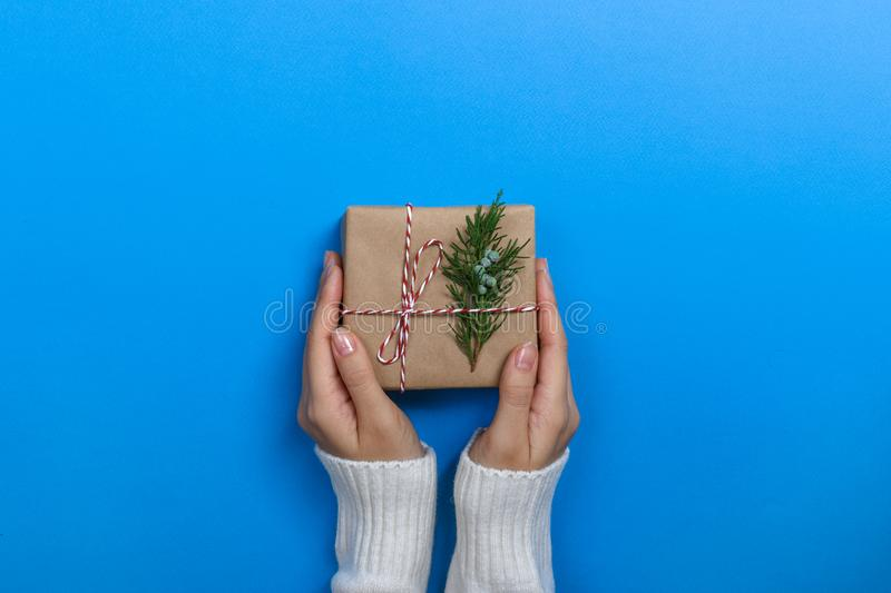 Female hands holding gift box on Blue background royalty free stock photo