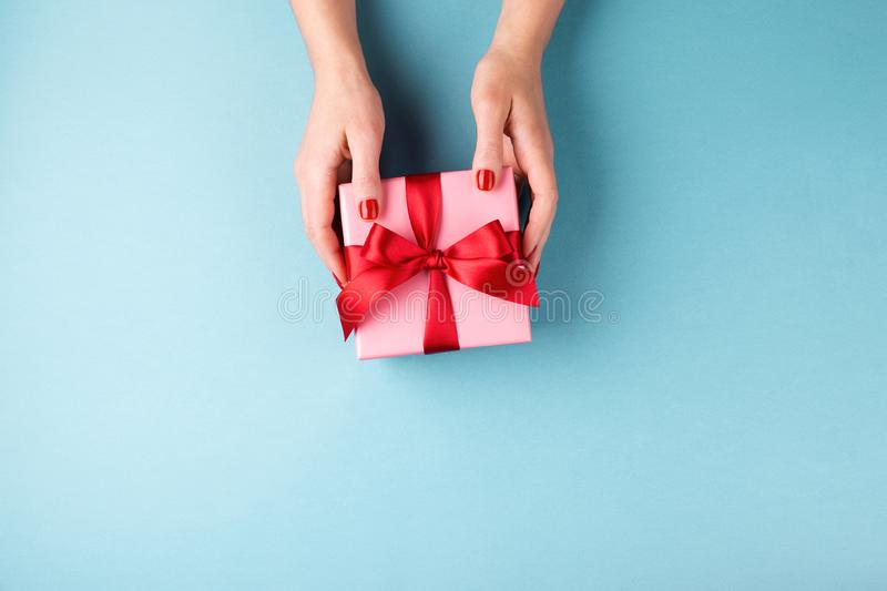 Female hands holding gift box on blue background. royalty free stock photo