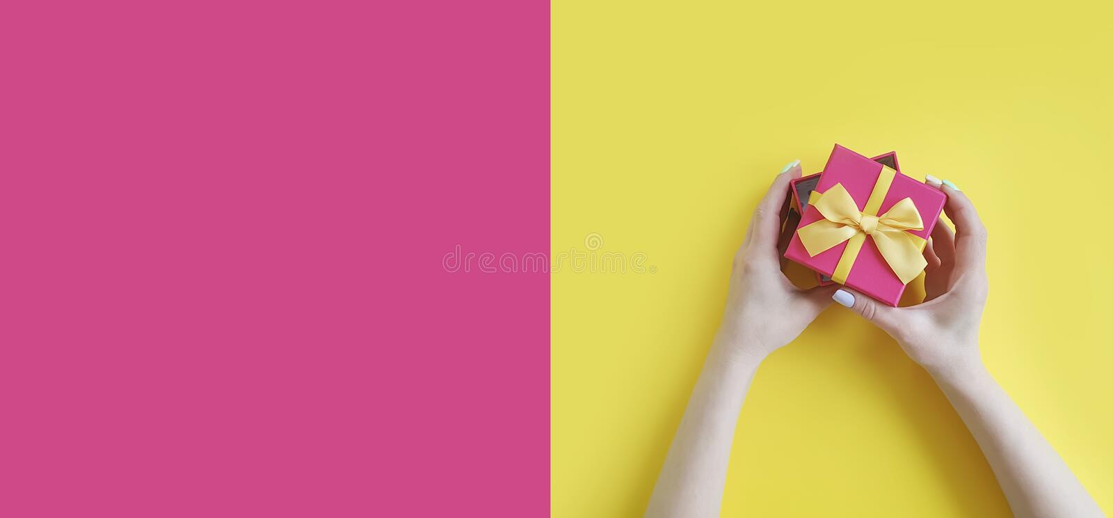 Female hands holding a gift box birthday on a colored background royalty free stock image