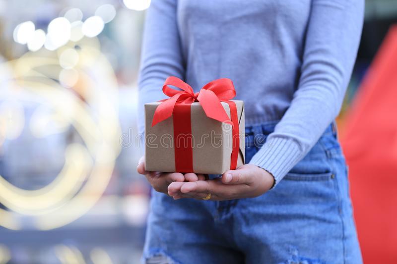 Female hands holding gift box with red ribbon for Christmas and New Year`s Day or Greeting season, Valentines day stock photography