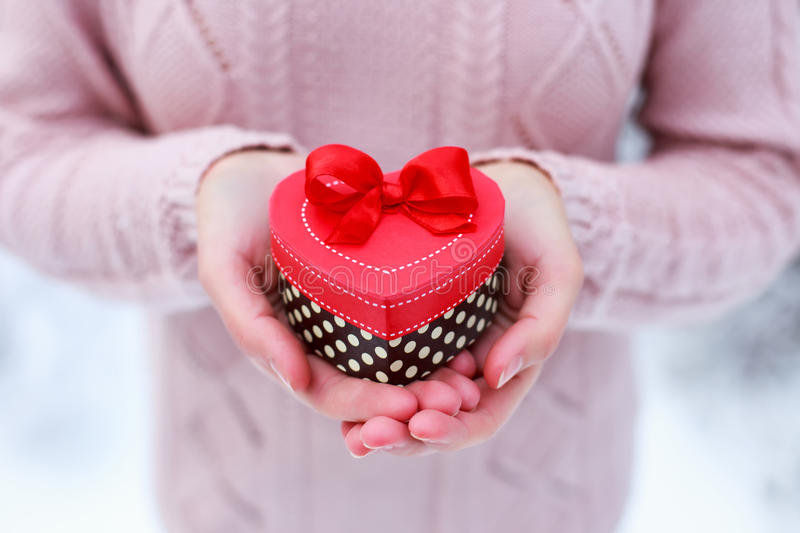 Female hands holding a gift box shaped of heart. The Valentines day and Christmas card. Female hands holding a gift box shaped of heart. The Valentines day and royalty free stock image