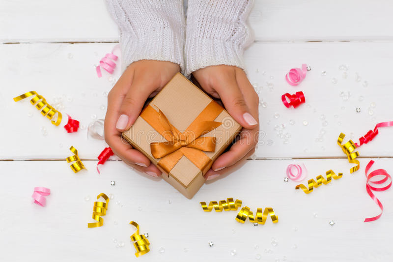 Female hands holding gift on white wooden table. Festive background for the holidays stock photos
