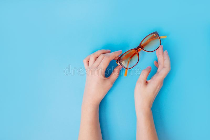 Female hands holding glasses on blue background. royalty free stock image