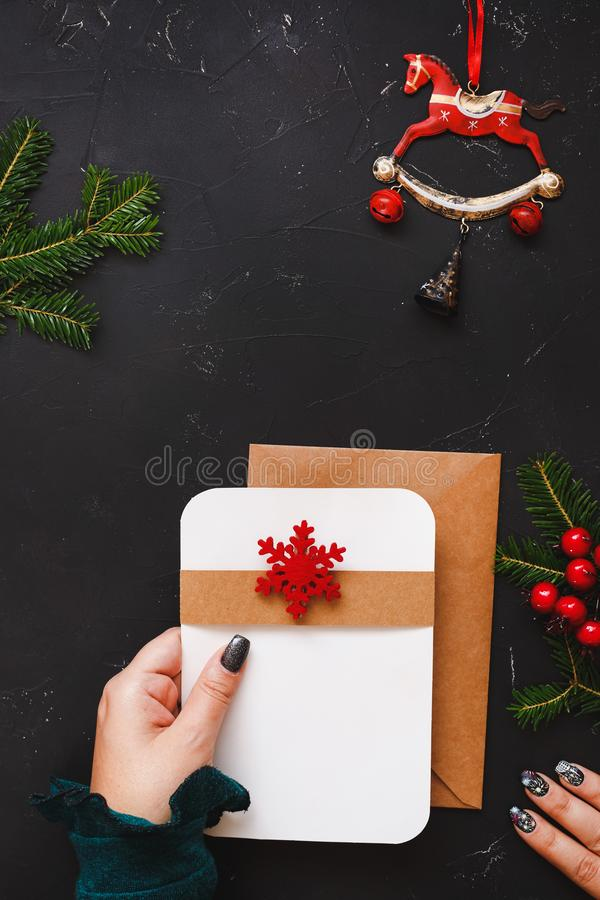 Female hands holding greeting card or letter over festive table royalty free stock photo