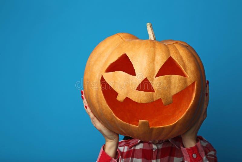 Hands holding halloween pumpkin. Female hands holding halloween pumpkin on blue background royalty free stock image