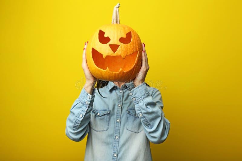 Hands holding halloween pumpkin. Female hands holding halloween pumpkin on yellow background stock photography