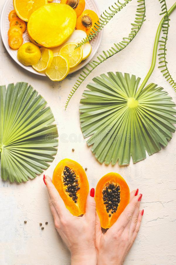 Female hands holding halved papaya fruit on white table with tropical leaves and plate with yellow sliced fruits, top view. Summer royalty free stock photography
