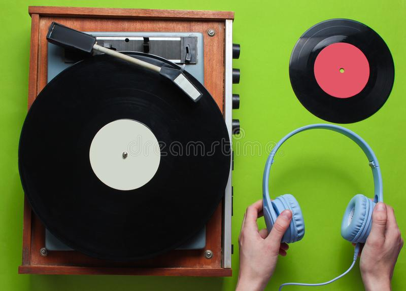 Female hands holding headphones against the background of retro vinyl record player with vinyl records on green background. stock images
