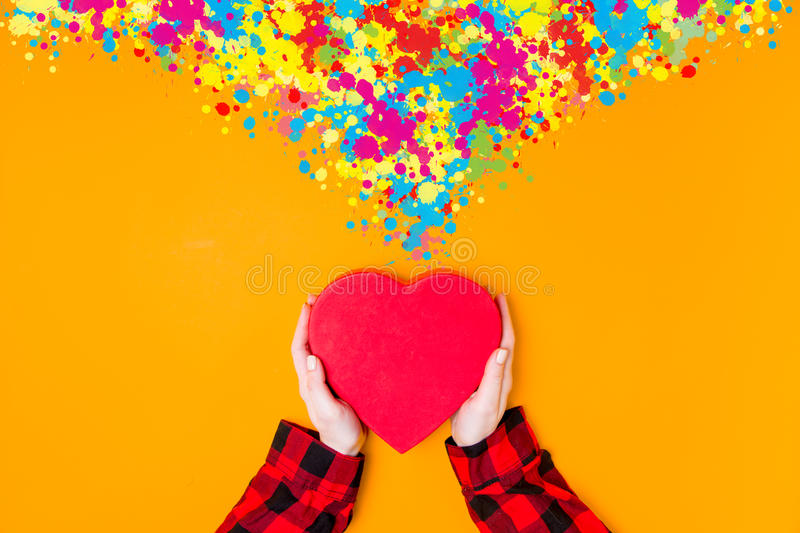 Female hands holding heart shape box with color inspiration. On yellow background royalty free stock image