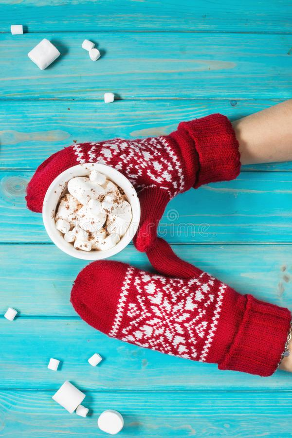 Female hands holding hot chocolate with marshmallow above blue wooden table royalty free stock photography
