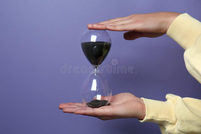 Female hands holding hourglass on color background stock photos