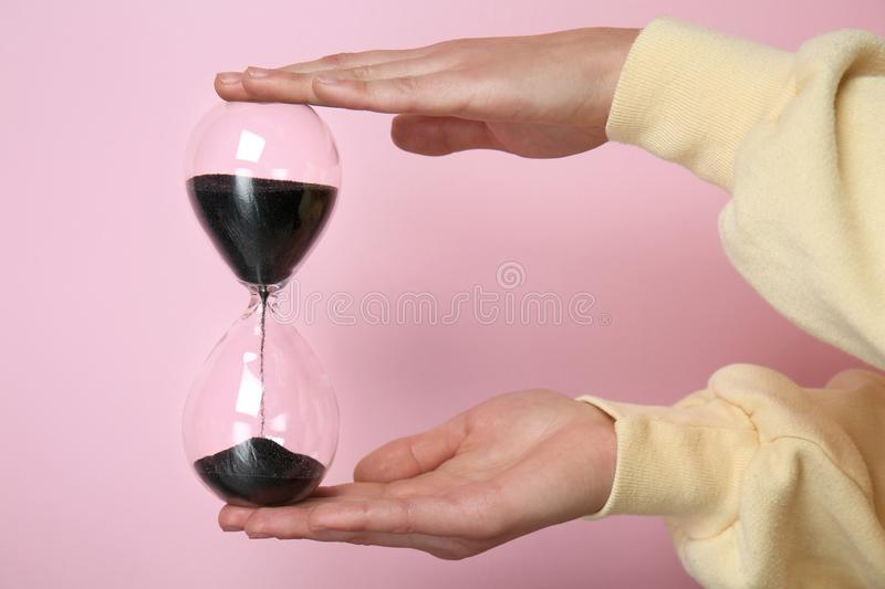 Female hands holding hourglass on color background royalty free stock photography
