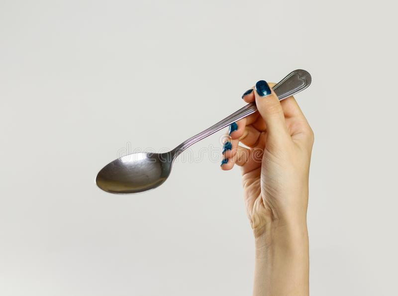 Female hands holding a metal tablespoon. Isolated on gray background. Closeup.  stock photo