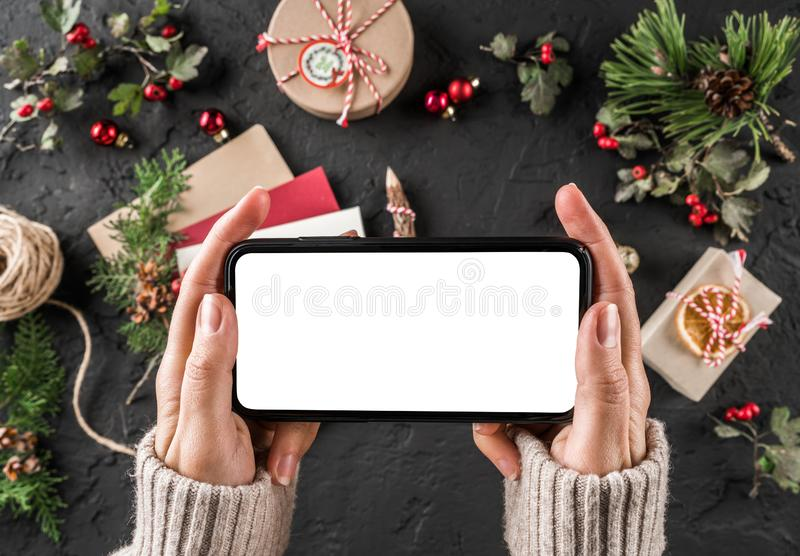 Female hands holding mobile phone. Christmas gift boxes with red decoration, Fir branches, pine cones on holiday background. royalty free stock image