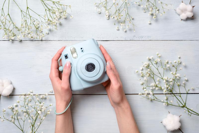 Female hands holding modern polaroid camera on a blue wooden background with flowers. Top view, tender minimal flat lay style comp. Osition. Womens desk, fashion royalty free stock image