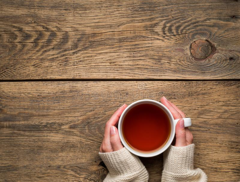 Female hands holding a mug of hot black tea. Cold winter white w royalty free stock image