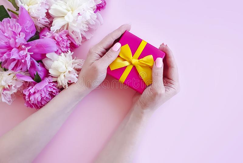 Female hands holding greeting a peony blossom flower gift box on a pink background stock photography