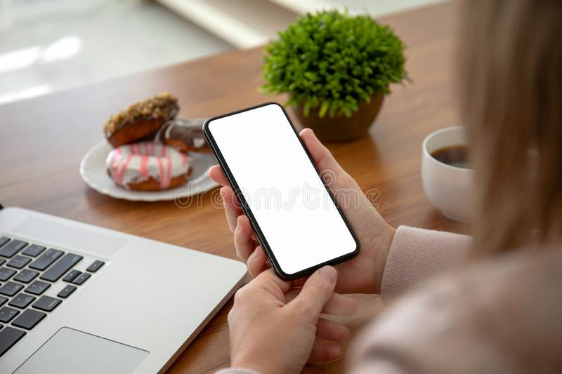 Female hands holding phone with isolated screen in the office stock photography