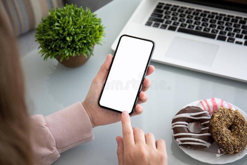 Female hands holding phone with isolated screen in the office royalty free stock photo