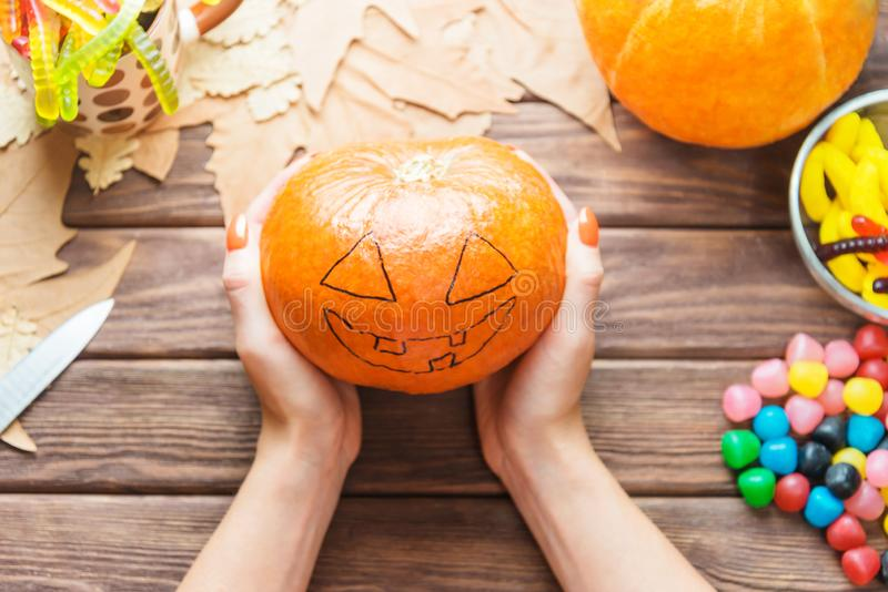 Female hands holding pumpkin with drawing Jack-o-lantern sketch. royalty free stock photography