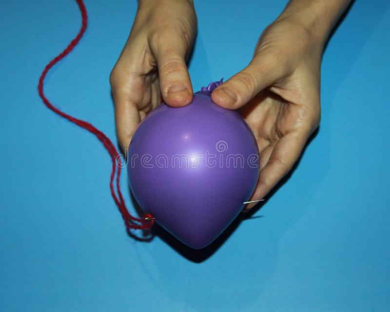Female hands holding a purple balloon pierced through and through with a sewing needle stock images