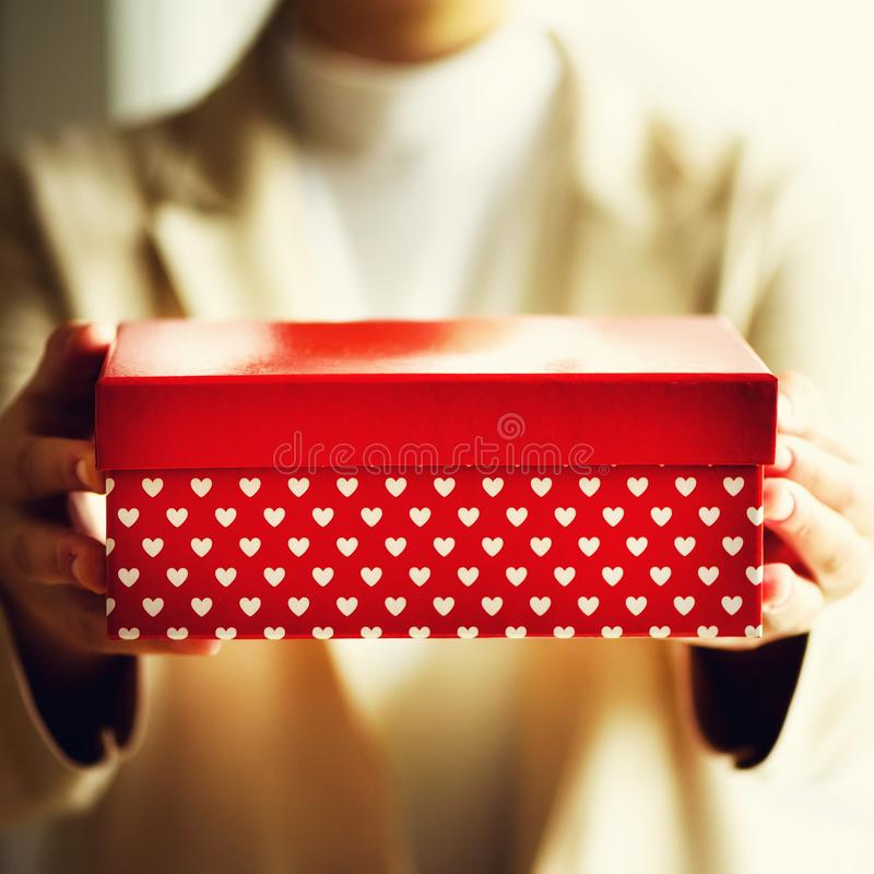 Female hands holding red gift box with white hearts, copy space. Christmas, hew year, birthday, valentines day concept. Square crop stock photography