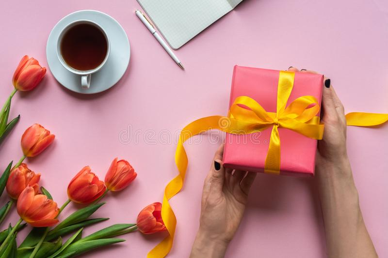 Female hands holding red gift box with yellow ribbon on pink background. Background with coffee, laptop and flowers. stock photos
