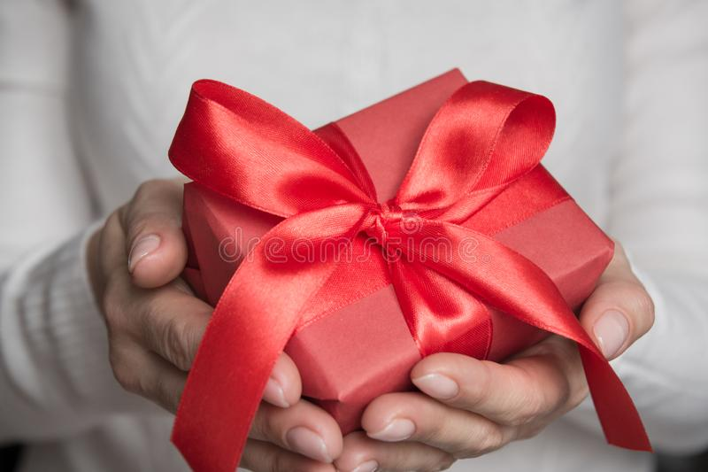 Female hands holding red gift wrapped with red bow ribbon. Close up. Xmas royalty free stock image
