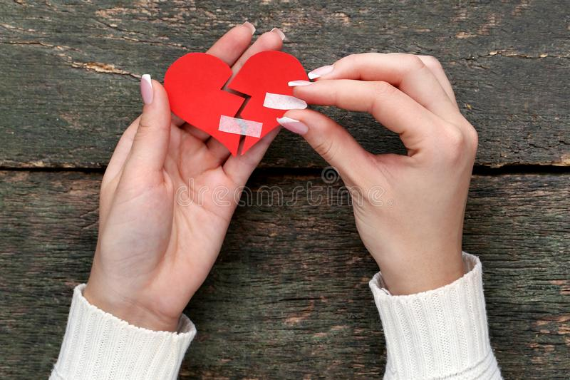 Hands holding paper heart stock photos