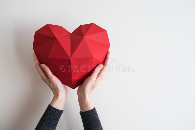 Female hands holding red polygonal heart shape. Two female hands holding red polygonal paper heart shape stock image