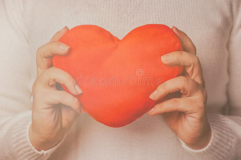 Female hands holding red toy heart. Valentines day concept. Retro toned picture. royalty free stock photos