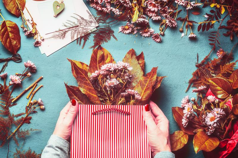 Female hands holding shopping bag with autumn flowers and leaves bunch on blue table background stock image
