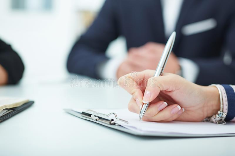 Female hands holding a silver pen and writing closeup. Business job offer, financial success, certified public. Female hands holding a silver pen closeup royalty free stock photography
