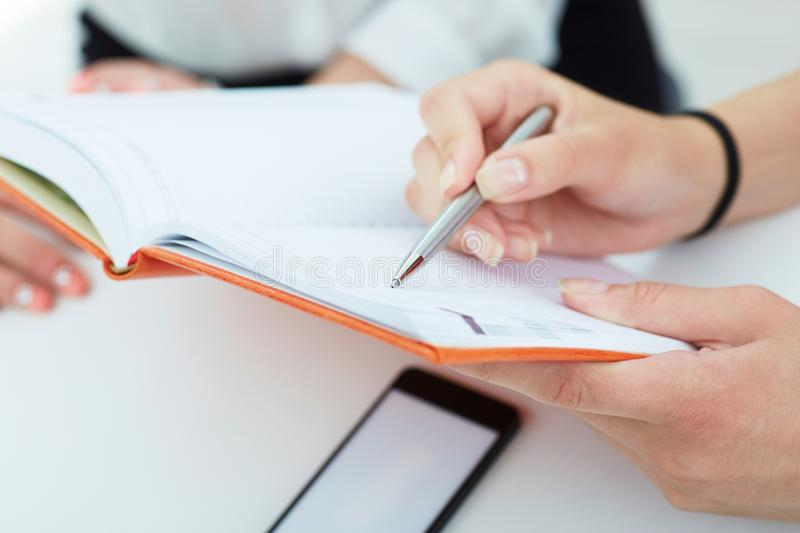Female hands holding a silver pen closeup. Business woman pointing at the record in notebook. royalty free stock photo