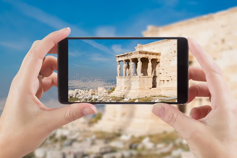 Female Hands Holding Smart Phone Displaying Photo of Caryatids i. N Erechtheum from Athenian Acropolis, Greece Behind royalty free stock photography