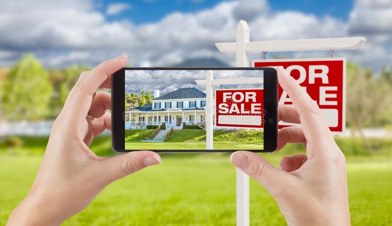 Female Hands Holding Smart Phone Displaying Photo of For Sale Re. Al Estate Sign and House Behind royalty free stock images
