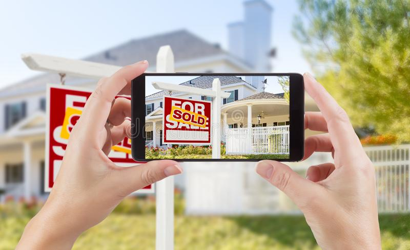Female Hands Holding Smart Phone Displaying Photo of Sold For Sa. Le Real Estate Sign and House Behind royalty free stock photography