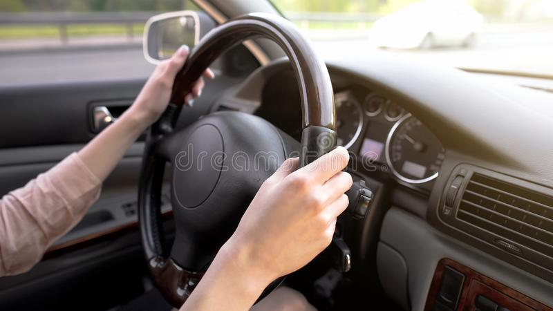Female hands holding steering wheel, woman driving car, comfortable vehicle stock photography