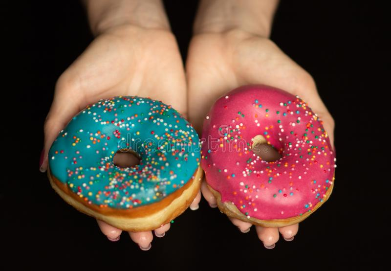 Female hands holding sweet donuts with sprinkles on black background stock image