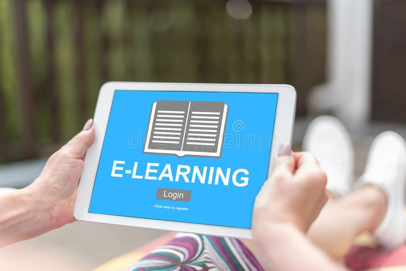 E-learning concept on a tablet. Female hands holding a tablet with e-learning concept royalty free stock photos