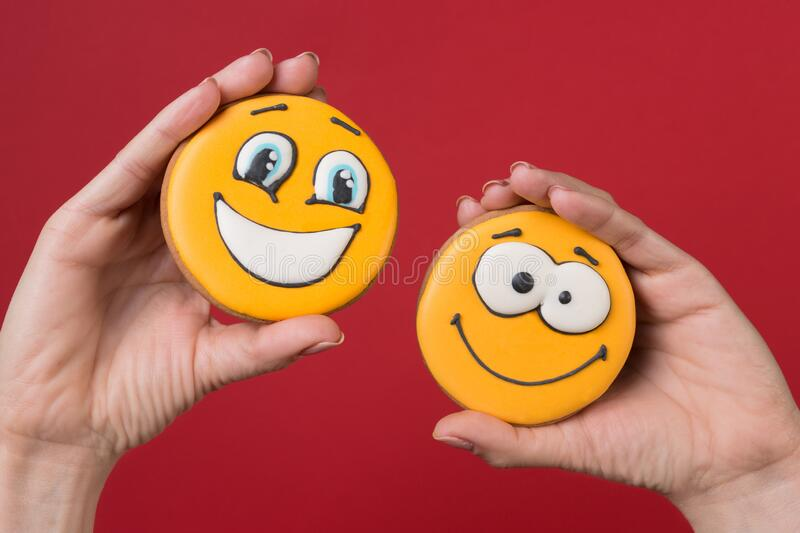 Female hands holding two yellow gingerbread cookies in the form of funny emoticons with emotions, concept. On red background stock photography