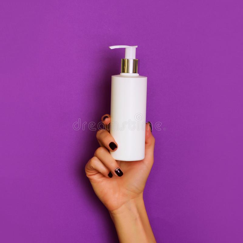Female hands holding white cosmetic bottle on violet background. Banner. Skin care, pure beauty, body treatment concept. Square stock photo