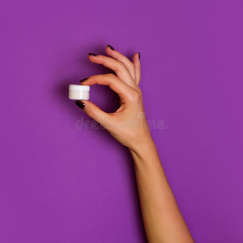Female hands holding white cosmetic bottle on violet background. Banner. Skin care, pure beauty, body treatment concept. Square stock images