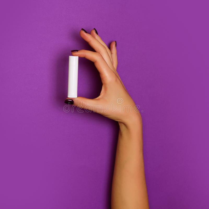 Female hands holding white cosmetic bottle on violet background. Banner. Skin care, pure beauty, body treatment concept. Square royalty free stock photo